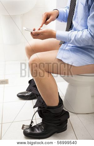 Business Man In Toilet Using Smart Phone Working