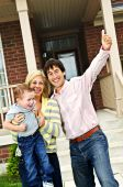 foto of overjoyed  - Young excited family celebrating in front of new home - JPG