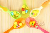 Plastic spoons with color pills on wooden background