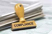 stock photo of statements  - compliance marked on rubber stamp at documents