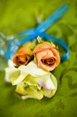 picture of boutonniere  - a silk boutonniere on a green tablecloth - JPG