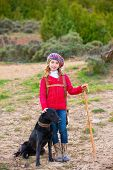 stock photo of shepherdess  - Kid girl shepherdess happy with dog flock of sheep and wooden stick in Spain - JPG