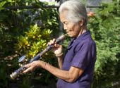 stock photo of hmong  - old Asian woman with opium pipe historical old pipe of hmong people - JPG