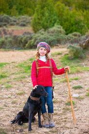 foto of shepherdess  - Kid girl shepherdess happy with dog flock of sheep and wooden stick in Spain - JPG