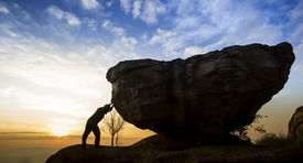 picture of fatigue  - Man pushing a boulder on a mountain - JPG