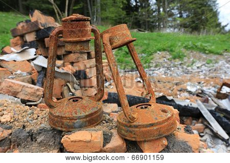 two old oil lantern on ruin after fire disaster