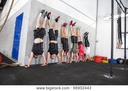 Team exercising handstands at fitness gym center