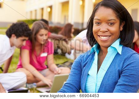 High School Teacher Sitting Outdoors With Students On Campus