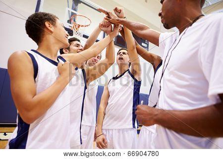 Male High School Basketball Team Having Team Talk With Coach