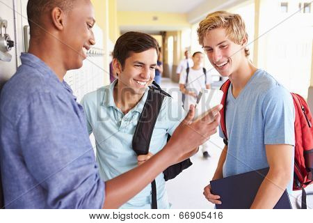 Male High School Students By Lockers Looking At Mobile Phone