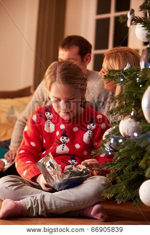 Girl Unwrapping Gifts By Christmas Tree