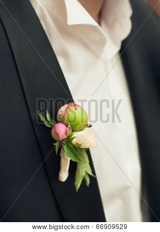pink peonies wedding boutonniere on suit of groom