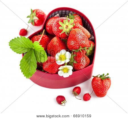fresh strawberries in box as heart with green leaf with green leaf. Isolated on white background