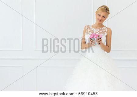 Wedding. Attractive bride holding pot with beautiful roses