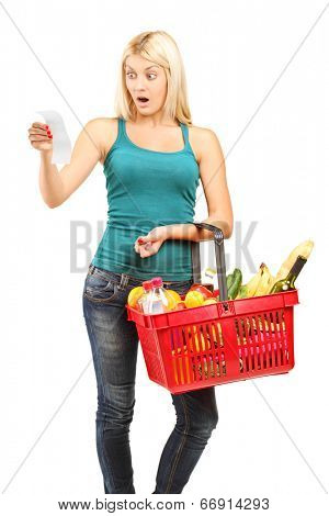 Shocked woman looking at the shopping bill and holding a shopping basket isolated on white background