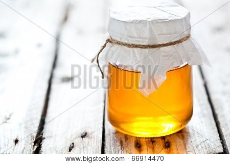 full honey pot on rustic wooden table