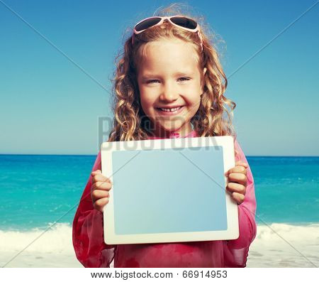 Child on the beach with tablet computer. Little happy girl showing screen digital pc