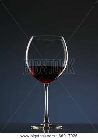 Elegant photo of a glass of red wine on dark background.