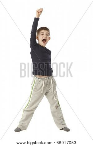 Little boy jittering, standing straddle, lifting right arm, shouting. Full size.