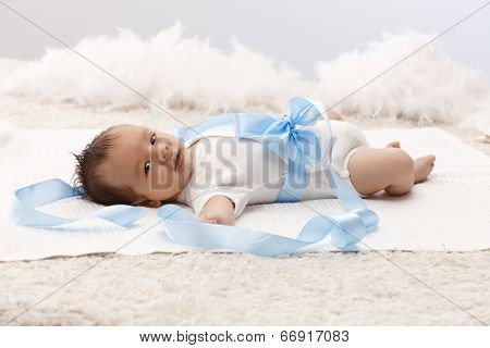 Beautiful baby lying on back in white bodysuit and blue ribbon around waist.