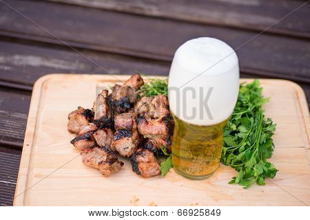 grill meat, green and beer on a woowen plate