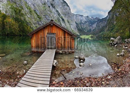 Cloudy day at Lake Koenigssee. Boathouse connected to the coast wooden decking. Clouds and mountains reflected in the water