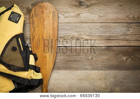 paddling concept - canoe paddle and life jacket against weathered wood with a copy space