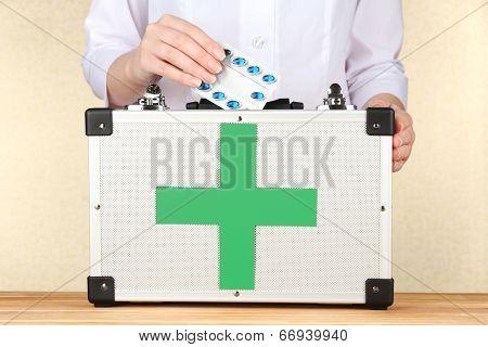 Nurse holding first aid kit, close up