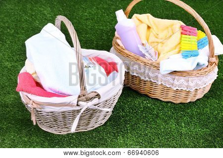 Colorful towels in baskets on green grass background