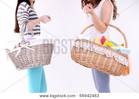 Women holding laundry baskets with clean clothes, towels and pins, isolated on white