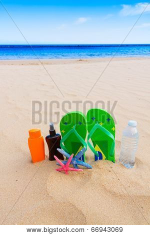 sandals and  bottle of water on sandy beach