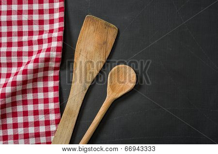 Wooden spoon on a blackboard with a red checkered tablecloth