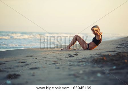 beautiful sunset young girl doing workout exercises on the beach