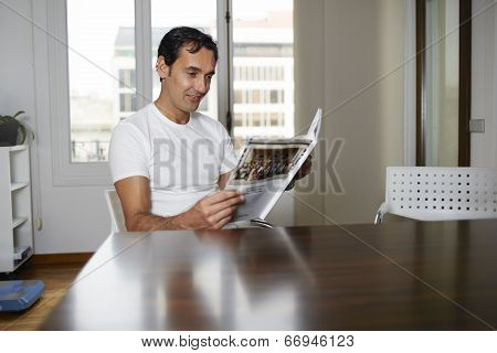 Handsome male reads magazine sitting behind a table