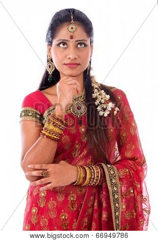 Portrait of beautiful young Indian female in traditional sari dress thinking, looking up, standing isolated on white background.