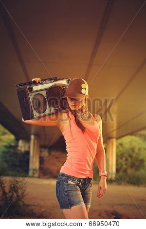 Hip Hop Woman With A Cap Which Holding A Tape Recorder On Shoulder. Toned Image.