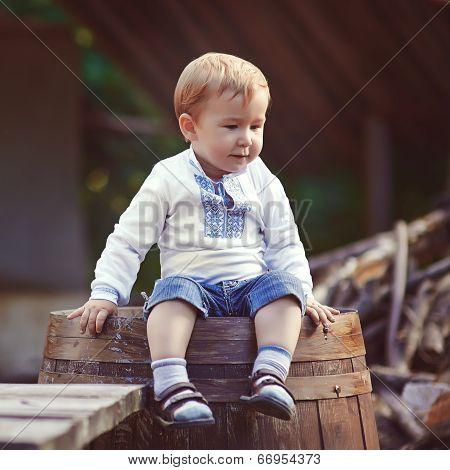 little boy sits on barrel in the village