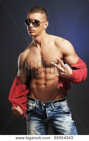 Handsome Young Man Takes Off His Shirt