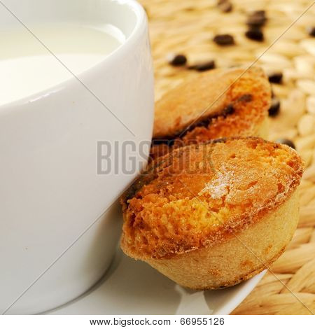 a cup with milk and some pasteis de feijao typical Portuguese pastries, on a set table