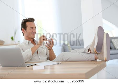 Relaxed man working from home and using smartphone