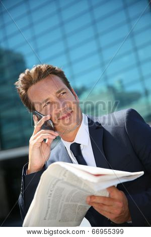 Businessman sitting outside office with smarphone and newspaper