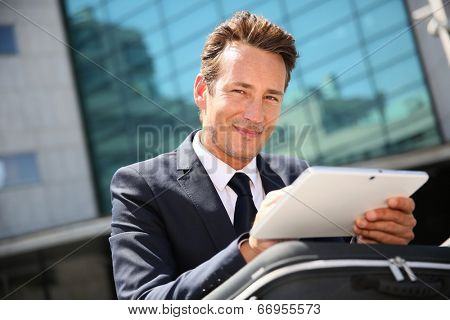 Businessman sitting outside office and using tablet