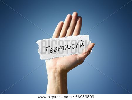 Man holding up a scrap of white paper with the word - Teamwork - in script, close up of his hand on a blue background with a side vignette in a conceptual image
