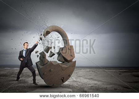 Businessman breaking stone lock with karate kick