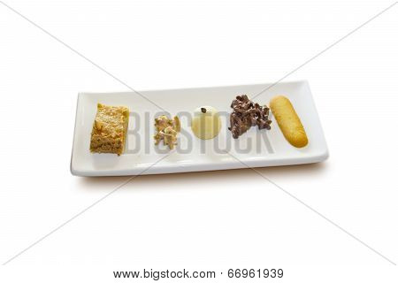 Variety of tasteful little cakes, displayed in a plate