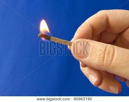 A hand holding a fired matchstick