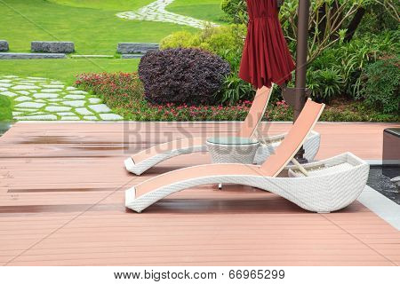 Wicker deck chair and table in the beautiful summer park with green lawns and flowerbed