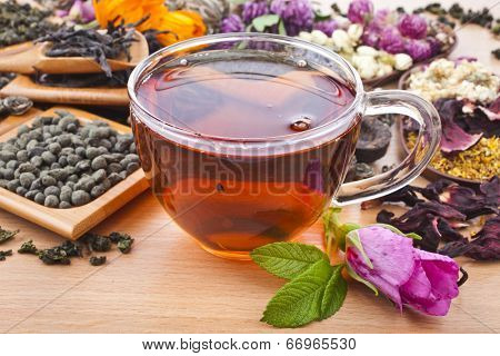 Tea glass cup and collection of different dry types tea (green,black, herbal) on kitchen wooden table background