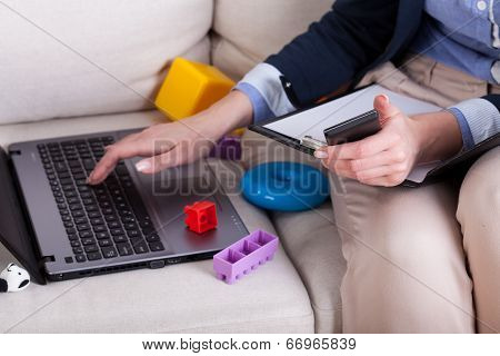 Female Hands Typing On Laptop And Kids Toys