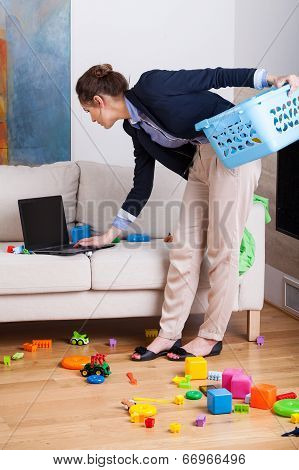 Woman Working On Her Laptop During Cleaning Up Living Room